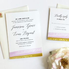 Wedding invitation suite features elegant, modern calligraphy and textured watercolor brushstrokes in lavender & ochre.